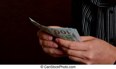 A businessman's hands counting hundred dollar bills
