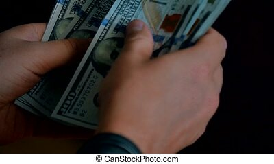 A businessman's hands counting hundred dollar bills close-up