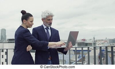 A businesspeople with laptop standing on a terrace, working...