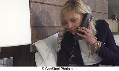 A businesswoman calls on the phone in a hotel room