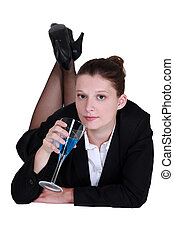 A businesswoman enjoying a cocktail laying on the floor.