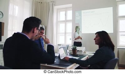 A businesswoman giving a presentation to colleagues in a modern office.