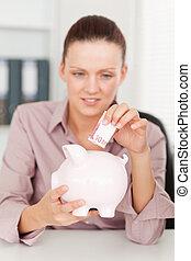A businesswoman inserting money in piggy bank