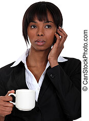A businesswoman over the phone drinking a coffee.