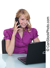 A businesswoman pleased by her phone conversation.