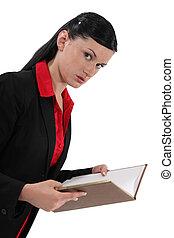 A businesswoman reading a book.