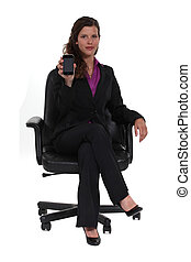 A businesswoman showing her cellphone.