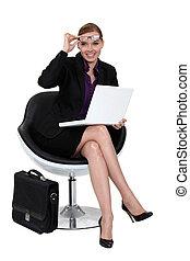 A businesswoman sitting in a modern chair.