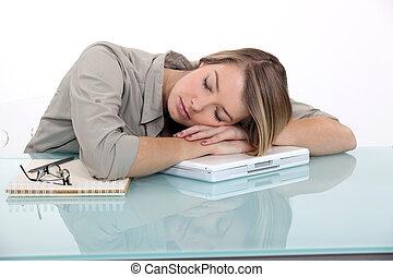 A businesswoman sleeping on her laptop.