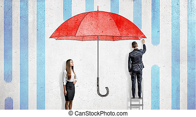 A businesswoman stands near a wall where a businessman draws a giant red umbrella covering them from the rain.