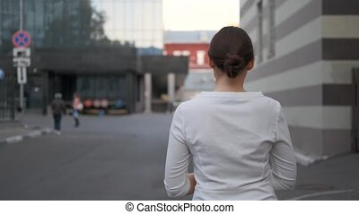 beautiful businesswoman walks down the street next to the Corporation building. A worker with a firm is walking down the street with a folder in his hands. Success, work in the company, colleague