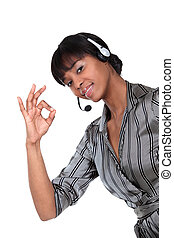 A businesswoman with a headset on making an ok sign.