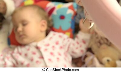 a byby sleeping in a cradle, toys are around, the mobile is...
