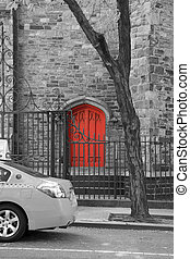 A cab is parking in front of a red door