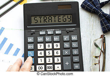 A calculator labeled STRATEGY lies on financial documents in the office. Business concept
