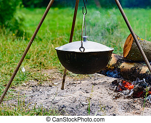 a camp-steaky sooty food bowl hanging on a tripod over a fire