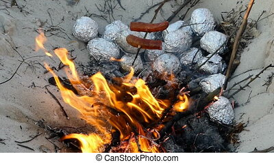 A campfire with potatoes wrapped in foil in summer - An...