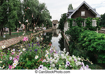 A canal in Strasbourg, France, with flowers