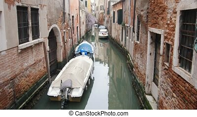 A canal on the streets of Venice. Moored boats. Mid shot