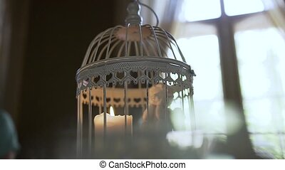 A candle in a lantern and a small decorative angel. Close up, of a burning candle in a flashlight