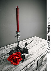 a candle in the candlestick in front of a rose