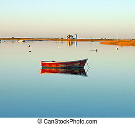 A dorey at sunrise casts a tranquil reflection at Chatham, Massachusetts.