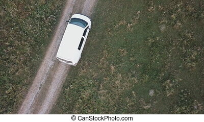 a car of white color rides on a dirt road