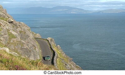 A car on a narrow road on a cliff over the sea - Wide shot...