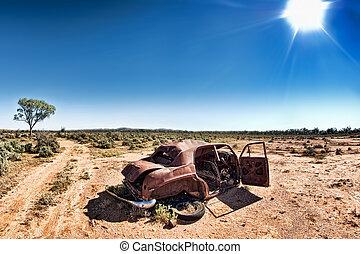 under a hot sun - a car rusts away under a hot sun in the...