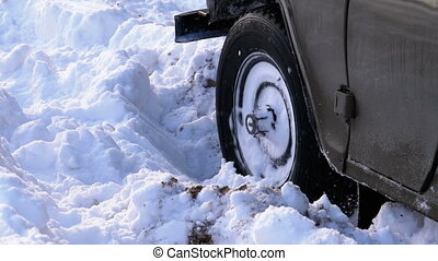 A car stuck in the snow turns the wheels. Wheel of a car...