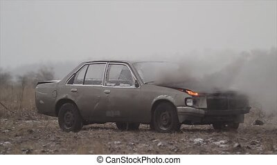 A car with a burning engine is in the field, smoke comes...