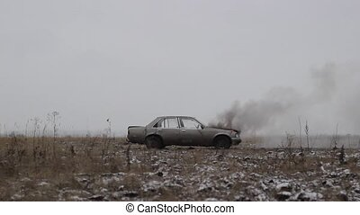 A car with a burning engine is standing in an open field,...