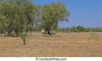 A caravan driving through dry bushland
