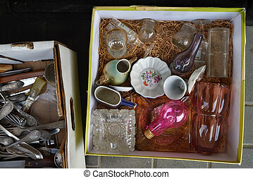 A cardboard box in which on glass sawdust glass glasses and plates of red and white color lie, in the next box metal forks, a black background.
