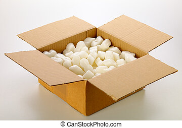A cardboard box with yellow packing styrofoam peanuts, ...