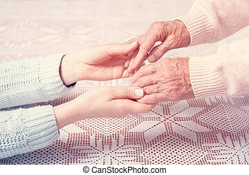 A care is at home of elderly. Holding hands closeup