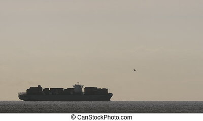 A cargo ship at dawn - A slightly moving cargo ship on the...