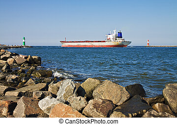 A cargo ship passes by the lighthouses of Warnemuende.