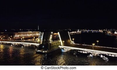 A cargo ship passes through a drawbridge at night, St. Petersburg video from a drone