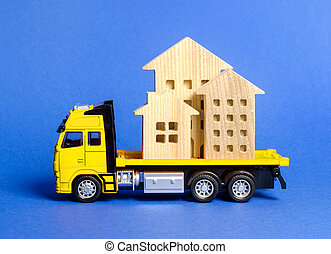 A cargo truck transports houses. Concept of transportation and cargo shipping, moving company. Construction of new houses and objects. Logistics and supply. Move entire buildings