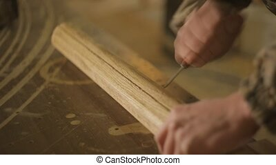 A carpenter carpenter performs with the help of a special tool, cycling, gives a roughness to a wooden product, workman
