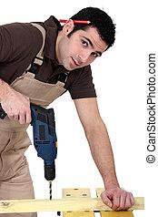 A carpenter drilling.