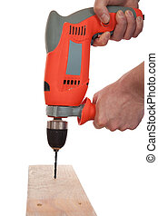 A carpenter is drilling a hole into a wooden board