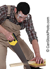 A carpenter sawing.
