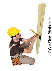 A carpenter taking measures.