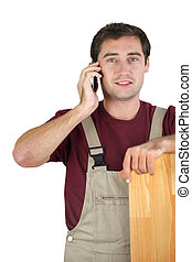 A carpenter talking on his mobile phone