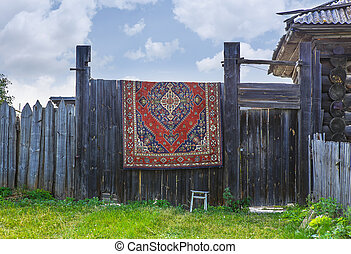 A carpet hangs on a wooden fence. - A carpet hangs on a...