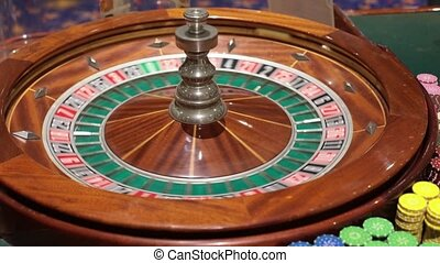 a casino dealer spins roulette hand - Roulette table and...
