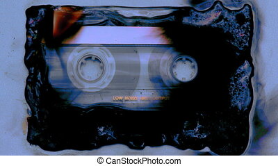 a cassette tape slowly being burnt and melting