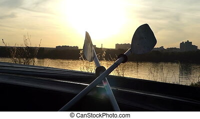 A catamaran boat with paddles on a lake bank at fine sunset